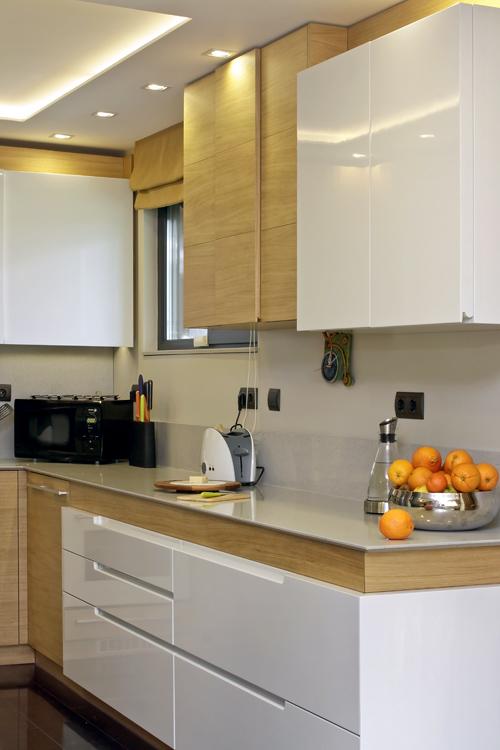 Вратичките на горния ред шкафове създават визуален 3 D ефект, който непринудено кореспондира с ламперията в хола. Визията е постигната с дизайн от плоскости с различни дебелини.